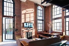 tall arched windows brick walls and a leather booth in this