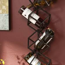 stacked black metal wine racks with cube shaped wine bottle placed