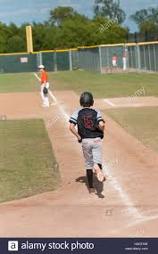 youth baseball kid running first base after a walk at home