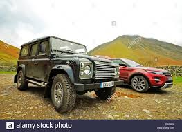 range rover defender land rover defender and range rover evoque parked at the foot of