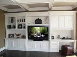 built in tv entertainment center and desk in den with coffer ceiling