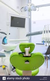 dental room with green chair modern led lamp and computer screen