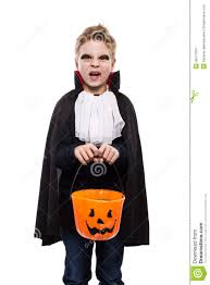 cute boy dressed as a vampire for halloween and holding a pumpkin