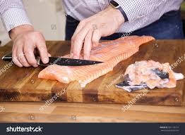 man preparing salmon fillet removing skin stock photo 561178714