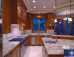 exterior granite countertop with wood cabinets and pendant