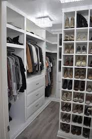 very well organized walk in closet with white cabinets and storage
