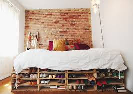 cozy small bedroom with a pallet bed frame serving as a shoe storage at