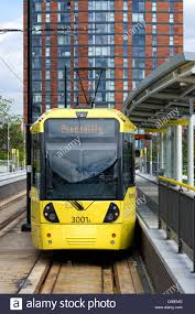 one of the modern yellow trams standing at a platform at