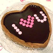 giant heart shaped cookie cake topped with fudgy chocolate ganache