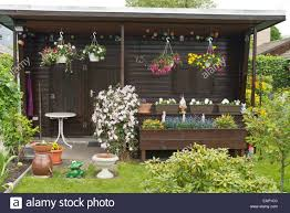 garden house with hanging baskets and window boxes stock photo