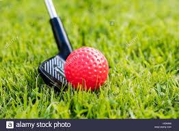 close up of golf stick hitting a plastic golf ball on grass stock