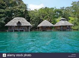 tropical shore with thatched bungalows over the water on the stock