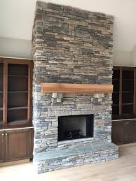 brick stone fireplaces between white wood bookshelves with small
