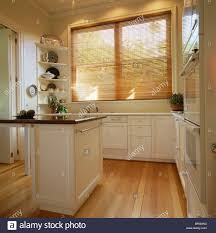 wooden venetian blind on window in modern white kitchen with