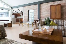 an exposed brick wall infuses this bright modern living room with