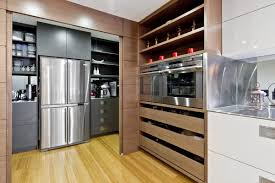 doors hiding grey cabinets and shelves with stainless steel double