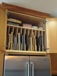 custom partition this is placed in the custom cherry cabinet slotted above the fridge storage is ideal for cutting boards cookie sheets and cooling racks brilliant idea for using the space above your refrigerator