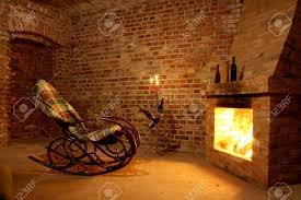 rocking chair by the fireplace in brick room with candles stock