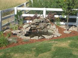 small diy ponds with waterfall and stone border in the corner