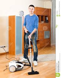 guy vacuuming with vacuum cleaner on parquet floor stock photo