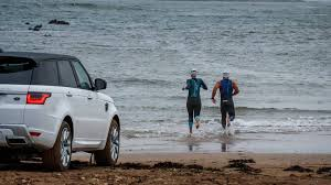 land rover water range rover sport phev wades into the sea races pro swimmers