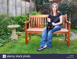a young woman sat on a garden bench with a cat on her lap stock