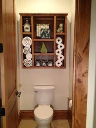 bathroom bathroom with brown wooden shelf over white toilet