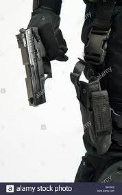 close up shot of a tactical police officer drawing his weapon from