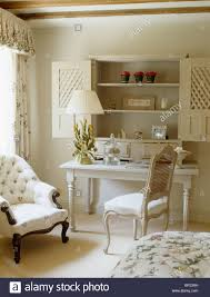 Button Back Armchair Wooden Shutters On Alcove Shelving Above Small White Table And