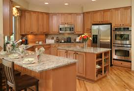 classic varnished oak wood galley kitchen with marble top island