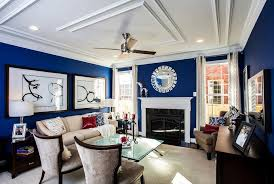 unique chrome round mirror in blue wall paint above fireplace for