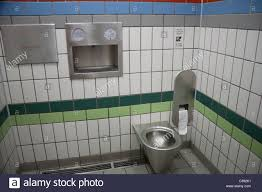 uk inside grey and green tiled public toilet with stainless steel