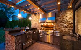 outdoor kitchen and living area by revision custom home