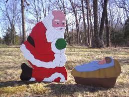 santa and baby jesus santa praising kneeling praying before manger crib with baby