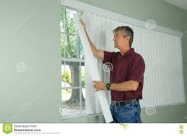 man hanging vertical blinds home repair maintenance stock photo
