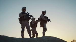 squad of three fully equipped and armed soldiers standing on hill