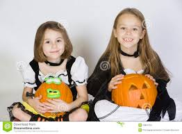 two girls dressed in halloween costumes holding jack o lanterns