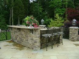 outdoor kitchen grills and rustic stone counter island with light