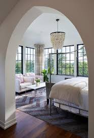 iron canopy bed with gray velvet settee transitional bedroom