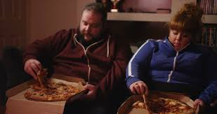 Fat Couch Potatoes 4k Overweight Couch Potato Couple Eating Takeaway Pizza In Front