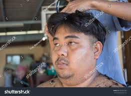 fat man getting haircut by hairdresser stock photo 382762339