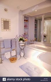 flowers in old french washstand in bathroom with mirror above bath flowers in old french washstand in bathroom with mirror above bath in alcove and mauve towels on heated towel rail