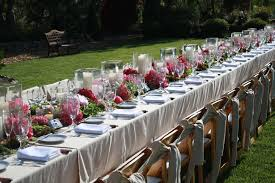 long table with white tablecloth combined by red flower bouquet