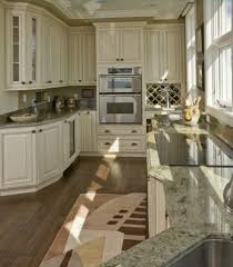 granite countertops kitchens with white cabinets and dark floors