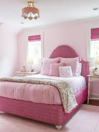 pink and blue vintage rug with white canopy bed transitional