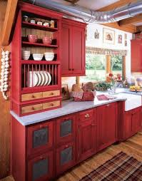 big metal refigerator in red kitchen cabinets facing black