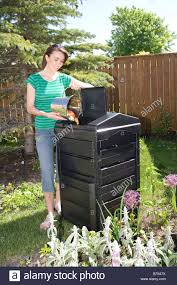 woman with compost pail beside composter in backyard winnipeg