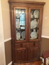 high end cherry queen anne lighted corner china cabinet in home
