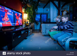 two young brothers sitting in front tv and playing video game