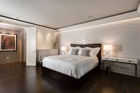contemporary master bedroom with hardwood floors by mosaic design